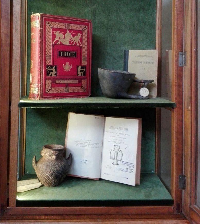 Ο πολυτελής τόμος του Ερρίκου Σλήμαν για τις ανασκαφές της Τροίας, άλλες εκδόσεις και αντίγραφα αρχαιοτήτων του 19ου αι., σε μία από τις προθήκες που σχεδιάστηκαν για την πρώτη έκθεση των Προϊστορικών Αρχαιοτήτων του Μουσείου.