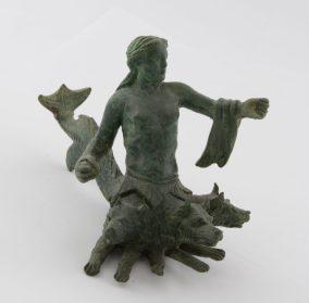 Χάλκινο ειδώλιο Σκύλλας που απειλεί με πέτρα τον αντίπαλο, ενώ τον αποκρούει με το αριστερό χέρι, κρατώντας πηδάλιο ή κουπί. Από το Καταφύλλι Καρδίτσας, τέλη 4ου αι. π.Χ.