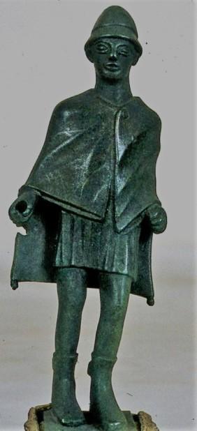 Ειδώλιο του θεού Ερμή με ένδυση βοσκού: βραχύ χιτώνα, χλαμύδα και κωνικό πίλο. Από το ιερό του Δία στο όρος Λύκαιο της Αρκαδίας. 5ος αι. π.Χ. (ΕΑΜ Χ 13219)